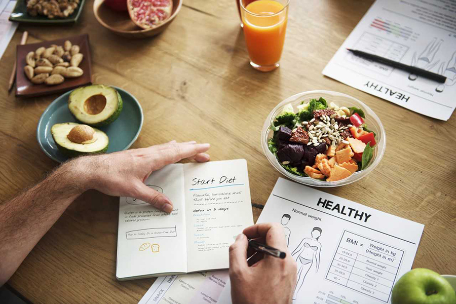 image of table with healthy food and man's hands planning diet