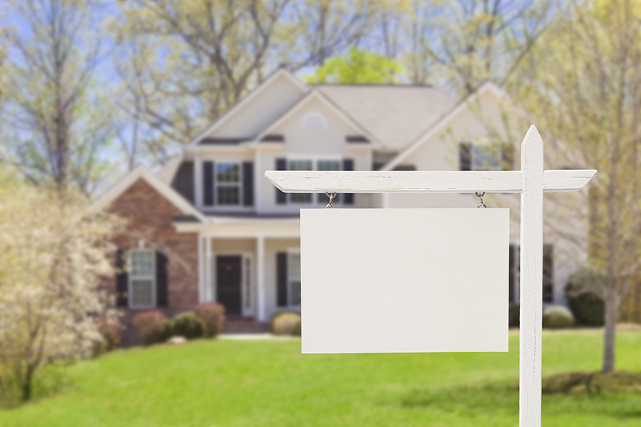 image of large home behind blank sign
