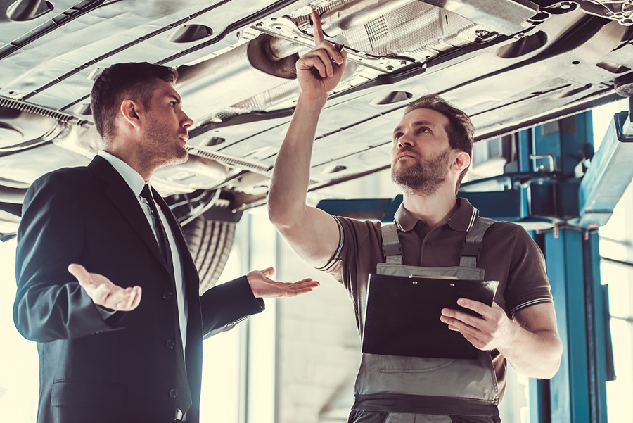 image of business man and mechanic under a car