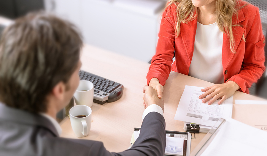 man and woman shaking hands across table and contract