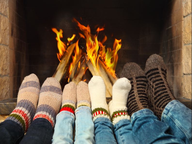 family feet warming on fireplace