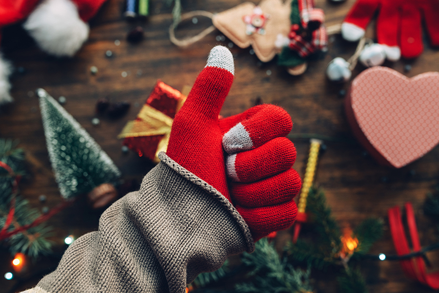 image of red gloved hand showing thumbs up for holidays